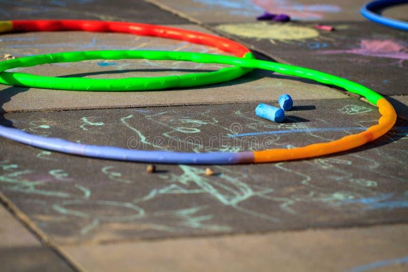 Pequeños aros del hula del juego de la muchacha en patio fotografía de archivo