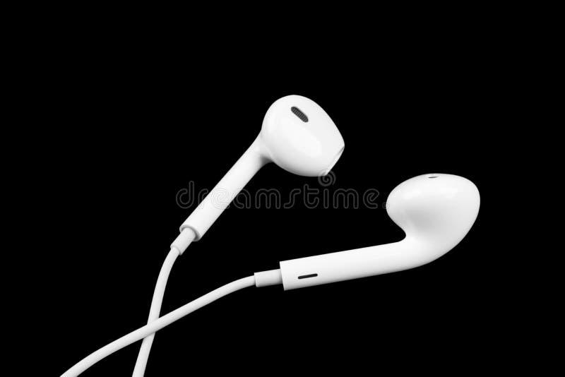 Pequeños auriculares blancos aislados en fondo negro Auriculares aislados en fondo negro imagen de archivo libre de regalías