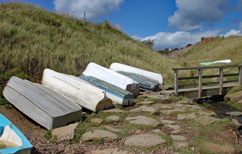 Pequeños barcos que reman vueltos hacia arriba por un pequeño puente por la costa en Eype en Dorset imagen de archivo libre de regalías