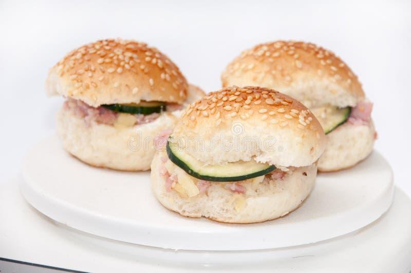 Pequeños bocadillos de la hamburguesa con el jamón y el pepino imagen de archivo