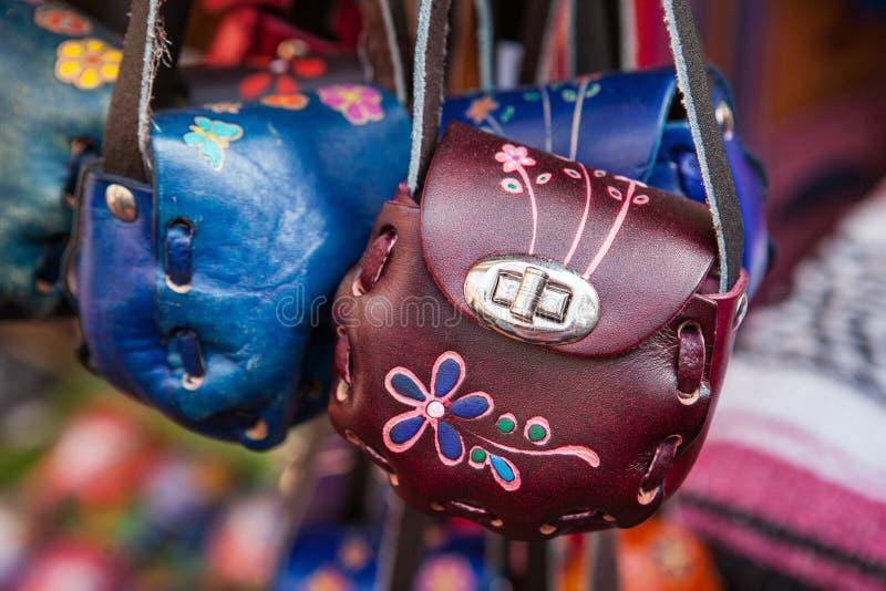 Pequeños bolsos de cuero coloridos hechos a mano en mercado mexicano fotografía de archivo libre de regalías