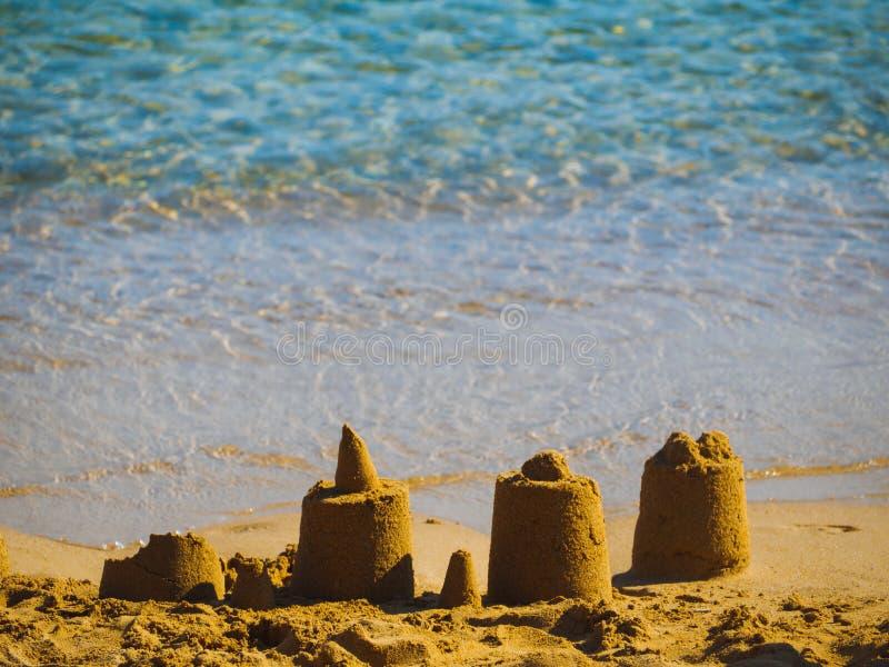 Pequeños castillos de la arena cerca del agua en una pequeña playa en Grecia foto de archivo