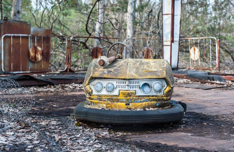 Pequeños coches oxidados de los niños en parque de atracciones abandonado en Pripyat, zona de exclusión de Chernóbil fotografía de archivo