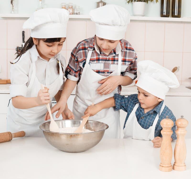 Pequeños cocineros felices que preparan la pasta en la cocina imagenes de archivo