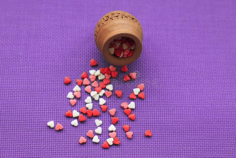 Pequeños corazones rojos, blancos y rosados dispersados de un florero de madera en un fondo violeta fotografía de archivo libre de regalías