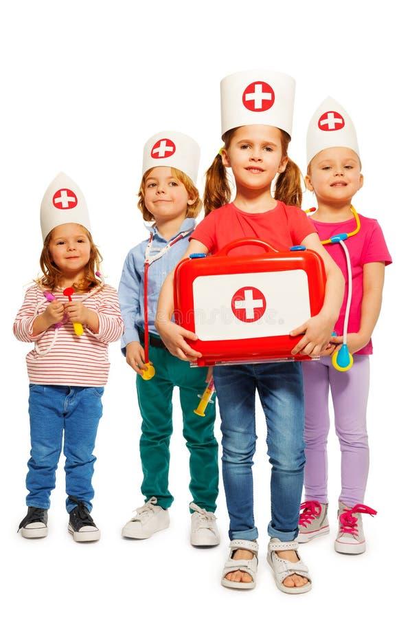 Pequeños doctores con la caja médica que da los primeros auxilios imagen de archivo libre de regalías