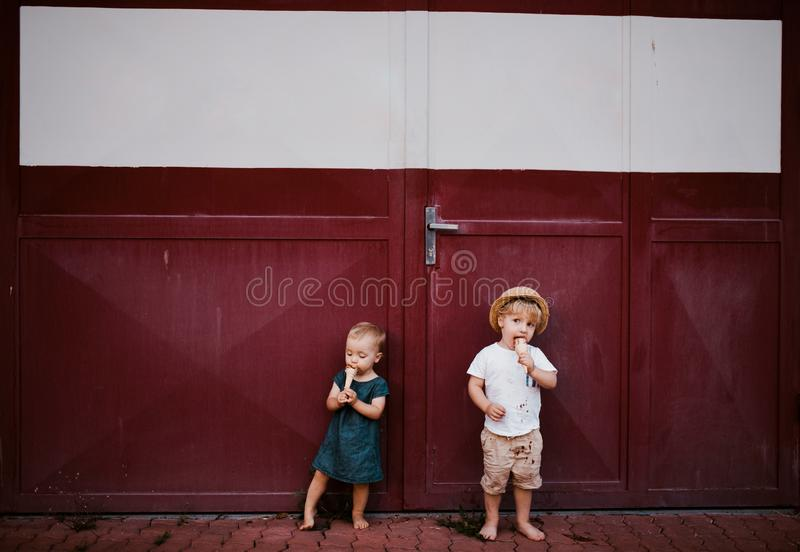 Pequeños dos niños del niño al aire libre en el verano, comiendo el helado imágenes de archivo libres de regalías