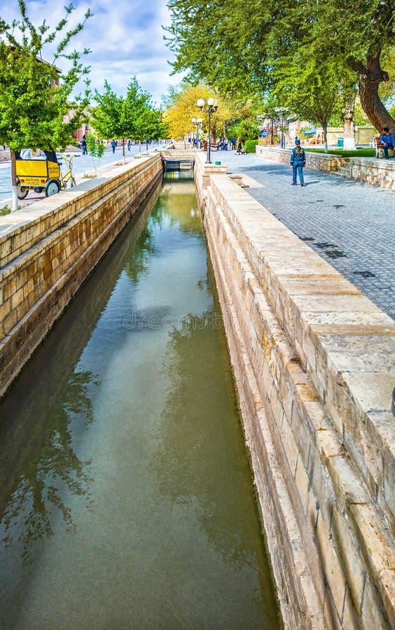Peque?os funcionamientos del canal a trav?s del coraz?n del centro de ciudad de Bukhara Uzbekist?n imagen de archivo