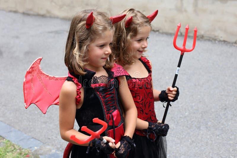 Pequeños gemelos rubios de la muchacha disfrazados como diablos imagen de archivo libre de regalías