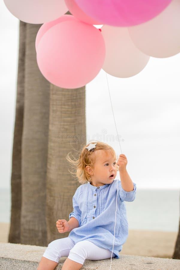 Pequeños globos rubios lindos del partido de la tenencia de la muchacha imágenes de archivo libres de regalías