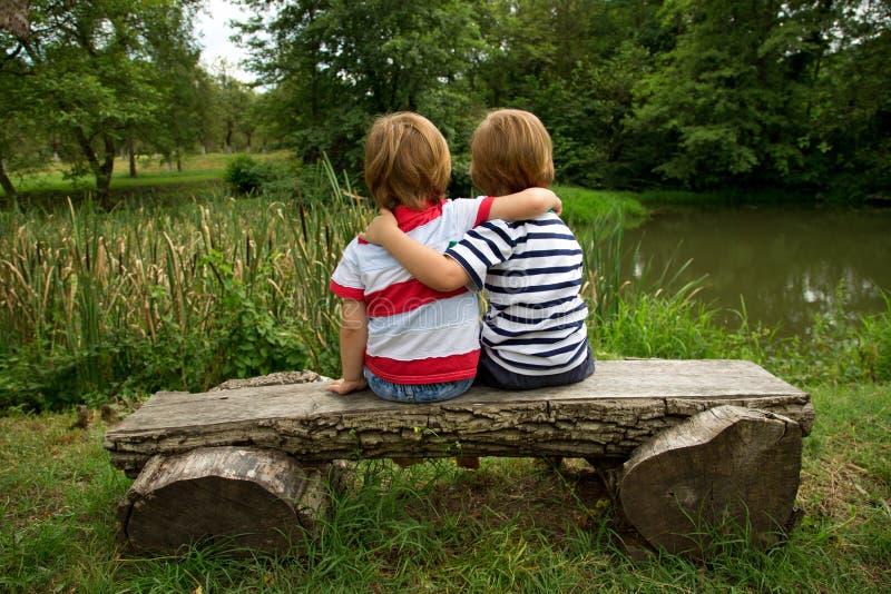 Pequeños hermanos gemelos adorables que se sientan en un banco de madera, abrazándose y mirando el lago hermoso foto de archivo