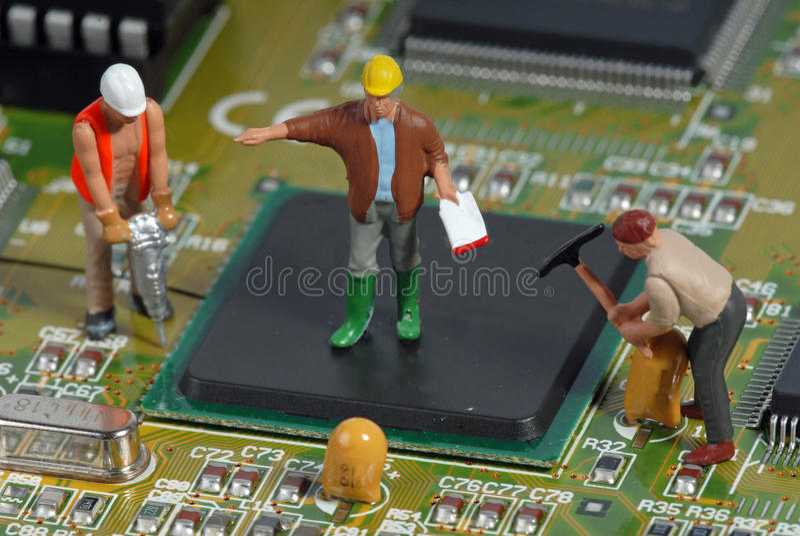 Pequeños hombres que reparan un ordenador imagen de archivo