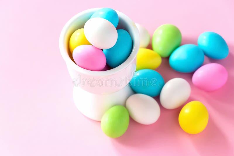Pequeños huevos de caramelo coloridos en el soporte Pascua celebra concepto Fondo rosado fotografía de archivo