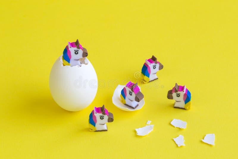 Pequeños juguetes del unicornio que salen de extracto de la cáscara de huevo imagen de archivo
