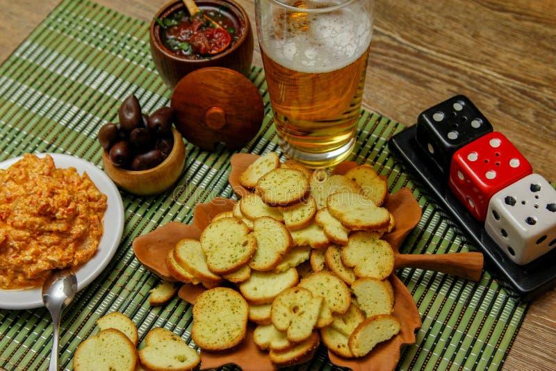 Pequeños microprocesadores de la tostada o del bruschetta de melba en la tabla de madera con la cerveza y las salsas imágenes de archivo libres de regalías