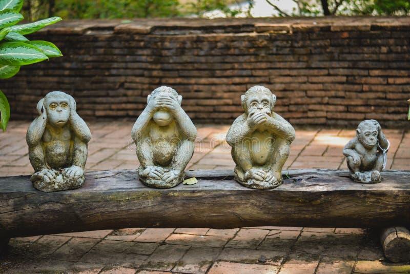 4 pequeños monos con una criba fotografía de archivo