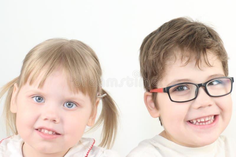 Pequeños muchacha y muchacho rubios felices en sonrisas de los vidrios imagen de archivo libre de regalías