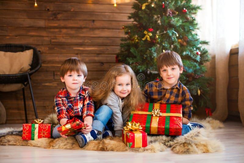 Pequeños muchacha y muchachos sonrientes felices con la caja de regalo de la Navidad fotografía de archivo