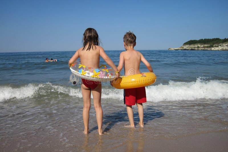 Pequeños muchacho y muchacha en la playa imágenes de archivo libres de regalías