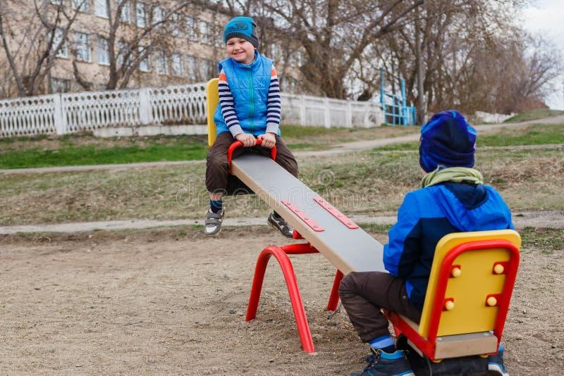 Pequeños muchachos divertidos que balancean en el oscilación en el patio en primavera imagen de archivo libre de regalías