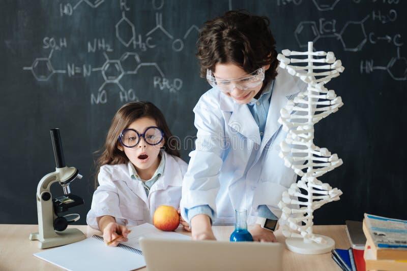 Pequeños niños abrumados que estudian la microbiología en la escuela foto de archivo