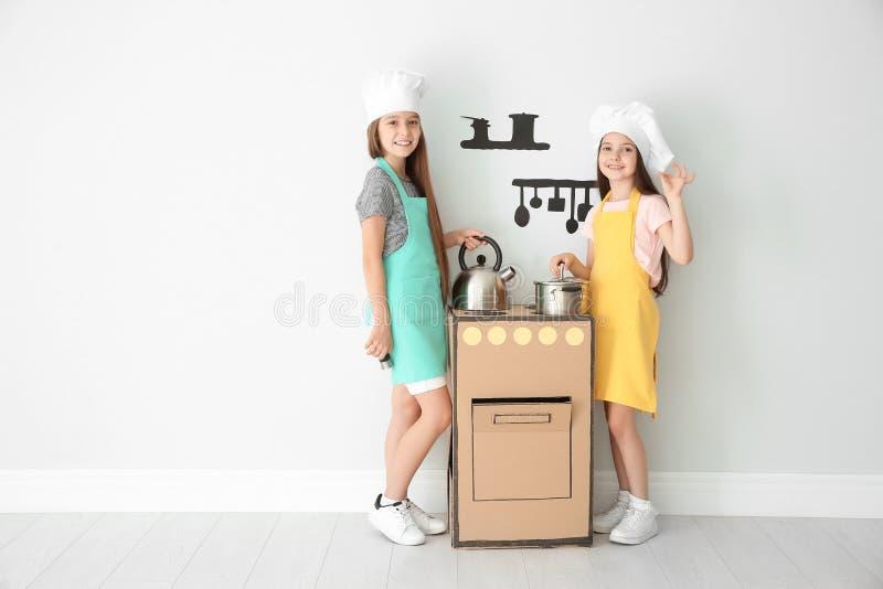 Pequeños niños en los sombreros del cocinero que juegan con la estufa del cartón foto de archivo