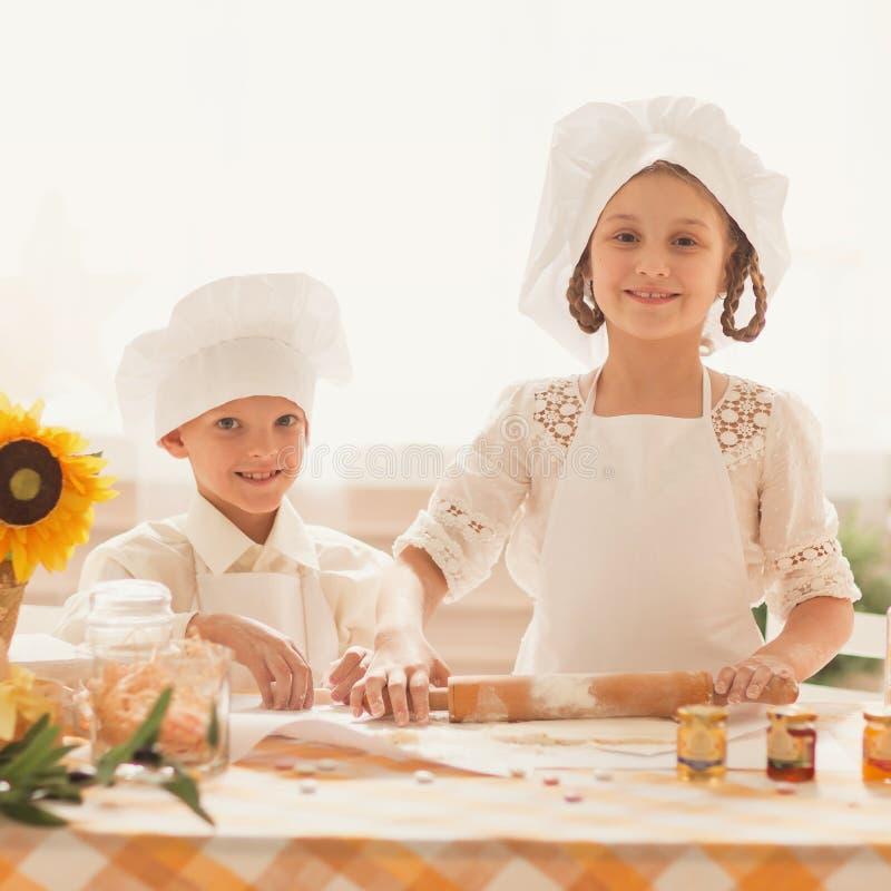 Pequeños niños felices bajo la forma de cocinero para cocinar la comida deliciosa imágenes de archivo libres de regalías