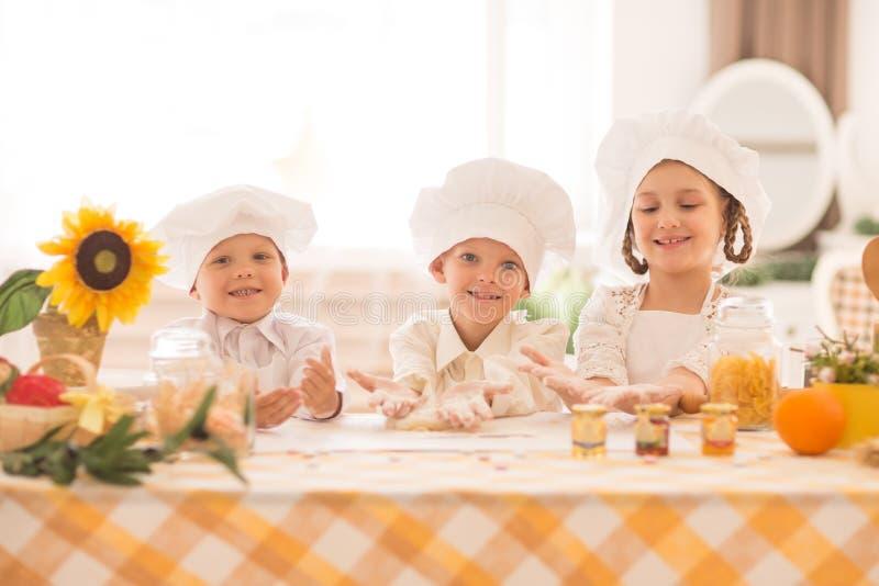 Pequeños niños felices bajo la forma de cocinero para cocinar un desayuno delicioso en la cocina imagen de archivo libre de regalías