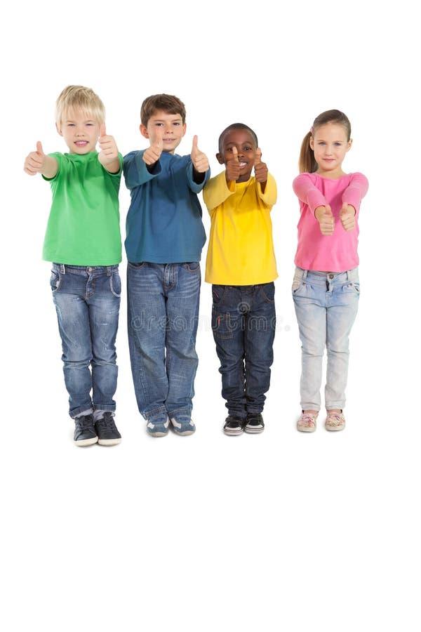 Pequeños niños felices que muestran los pulgares para arriba imagen de archivo