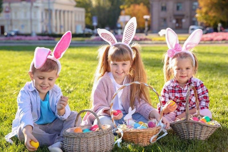 Pequeños niños lindos con los oídos del conejito y las cestas de huevos de Pascua fotos de archivo