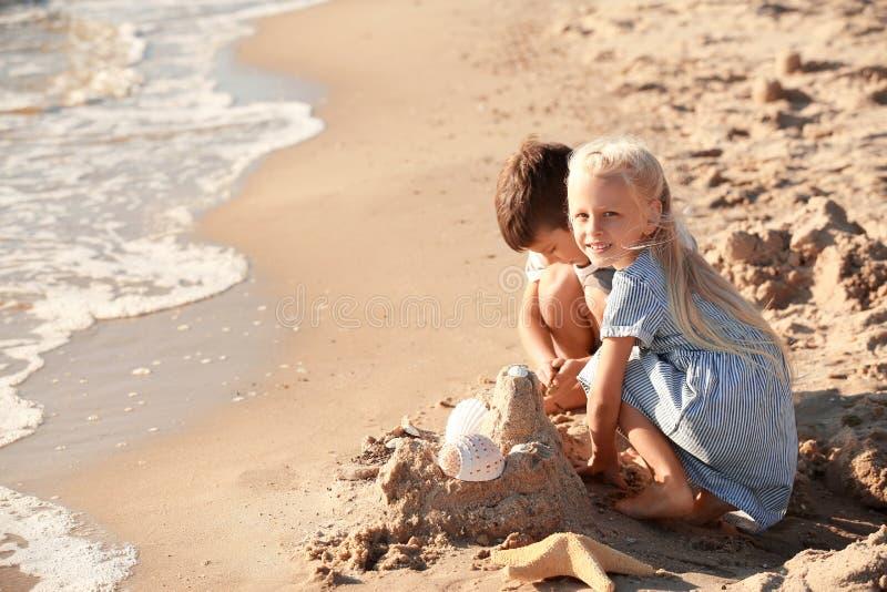 Pequeños niños lindos que construyen el castillo de la arena en la playa del mar imagen de archivo