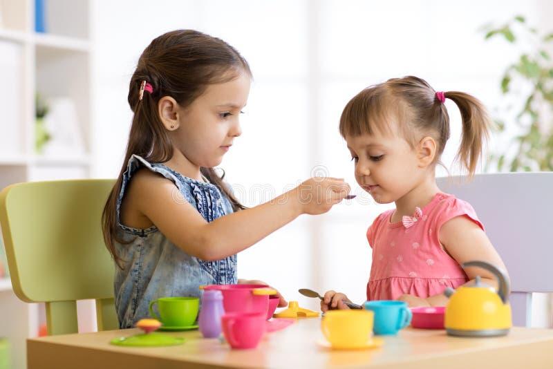 Pequeños niños lindos que juegan con artículos de cocina mientras que se sienta en la tabla en casa o la guardería foto de archivo