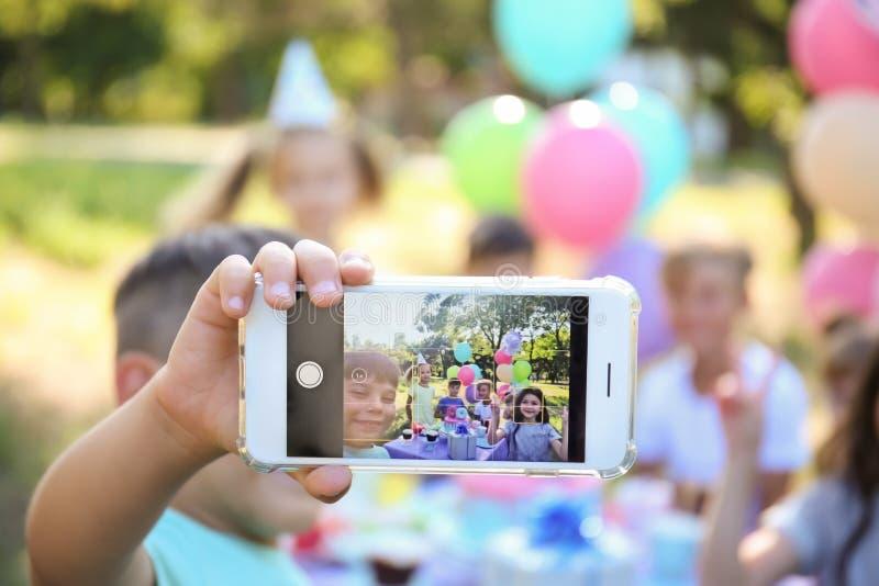 Pequeños niños lindos que toman el selfie en la fiesta de cumpleaños al aire libre imagen de archivo libre de regalías