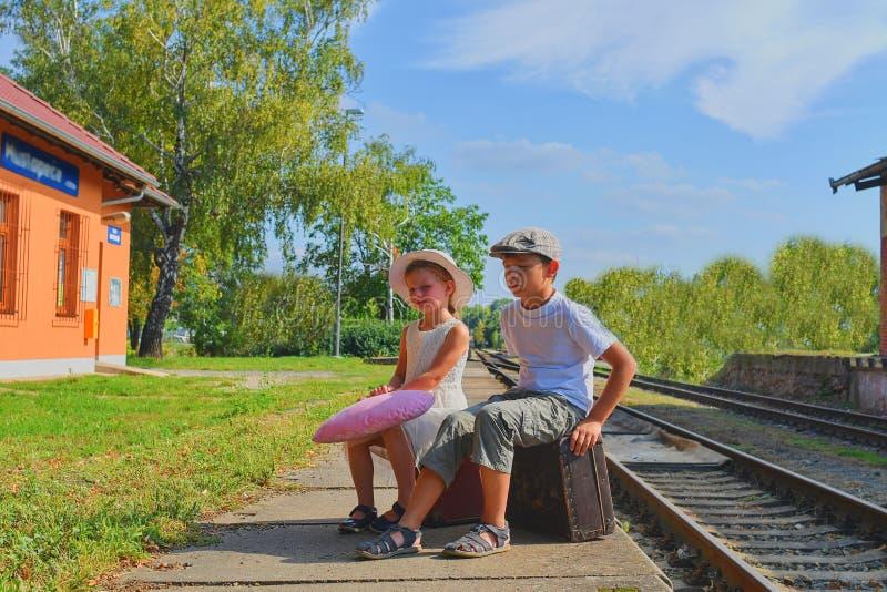 Pequeños niños - muchacha y muchacho en un ferrocarril, esperando el tren con la maleta del vintage El viajar, día de fiesta y ch fotos de archivo