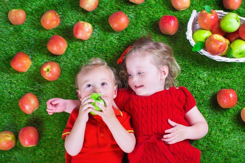 Pequeños niños que comen manzanas imagenes de archivo