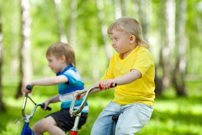 Pequeños niños que montan sus bicis fotografía de archivo libre de regalías