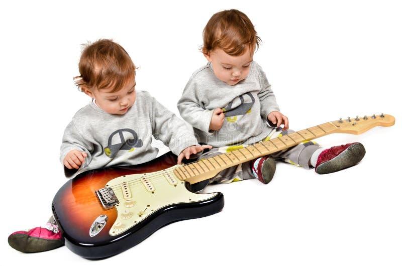 Pequeños niños que tocan la guitarra eléctrica imágenes de archivo libres de regalías