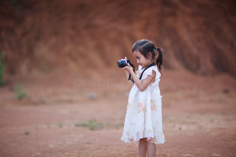Pequeños niños que toman la foto por la cámara mirrorless imagenes de archivo