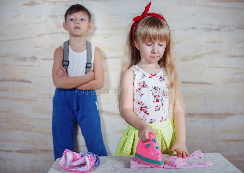 Pequeños niños serios que juegan la casa imagen de archivo