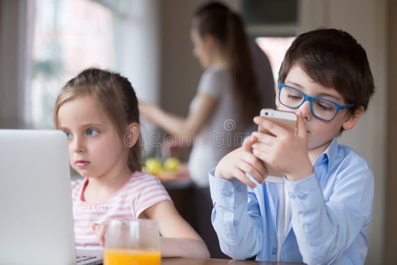Pequeños niños usando los artilugios que juegan a juegos o que miran el vídeo imagenes de archivo