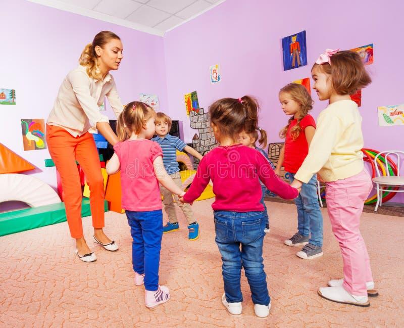 Pequeños niños y canción con estribillo del profesor en la lección foto de archivo libre de regalías
