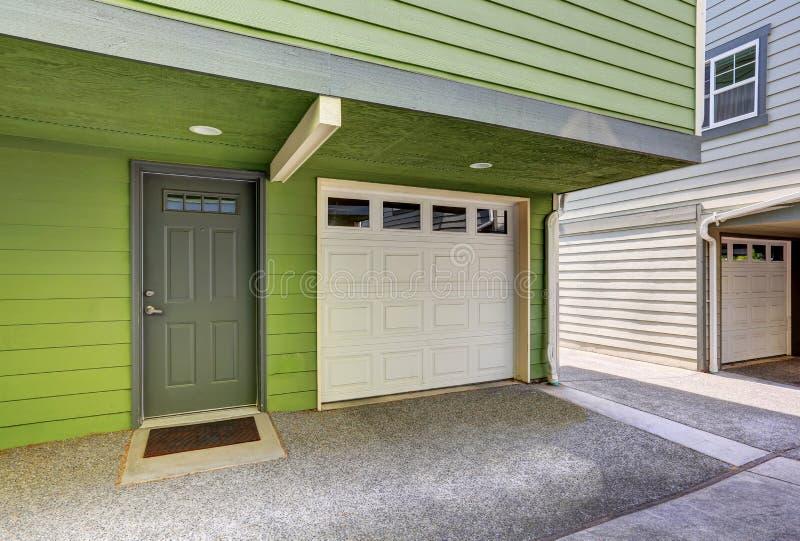 Pequeños pórtico de la entrada y puerta del garaje de la casa a dos caras imagen de archivo