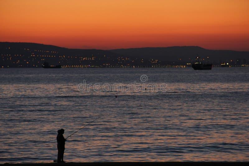 Pequeños pescadores en el mar en la puesta del sol fotografía de archivo