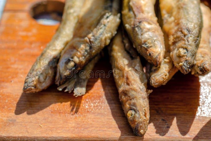 Pequeños pescados fritos frescos Mariscos deliciosos en un fondo de madera imagenes de archivo