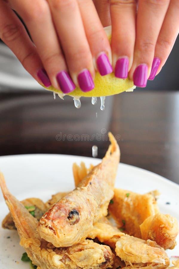Pequeños pescados fritos limón foto de archivo