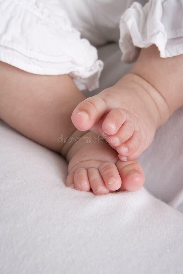 Pequeños pies del bebé en cama fotografía de archivo