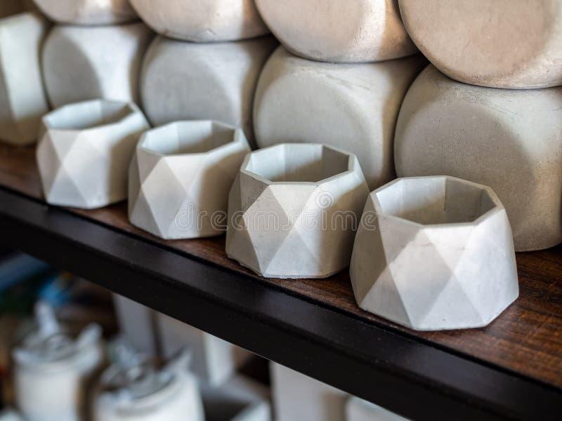 Pequeños plantadores concretos geométricos en estante de madera Potes concretos para la decoración casera fotografía de archivo