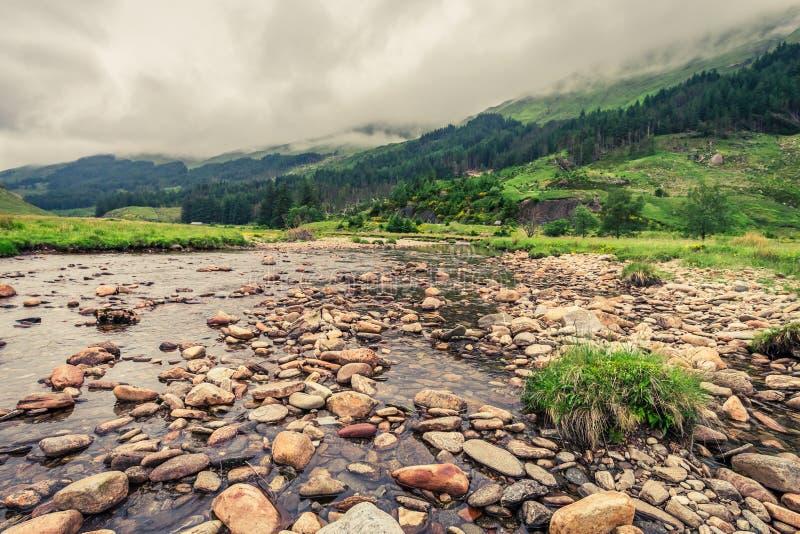 Pequeños río y montaña en un día de niebla imagenes de archivo