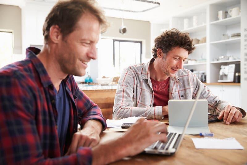 Pequeños socios comerciales que usan los ordenadores en casa foto de archivo libre de regalías