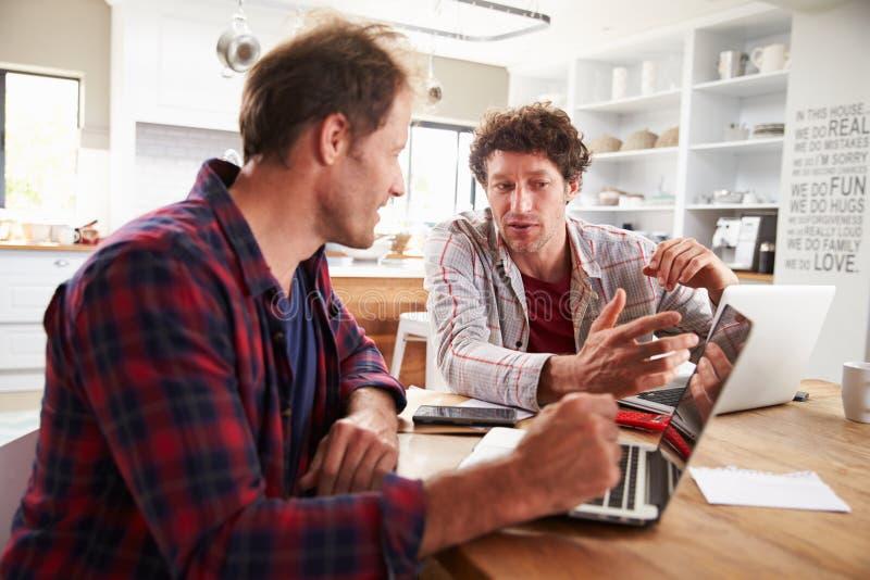 Pequeños socios comerciales que usan los ordenadores en casa imagen de archivo